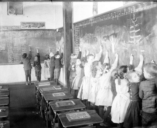 grade-school-classroom-with-students-writing-on-blackboard